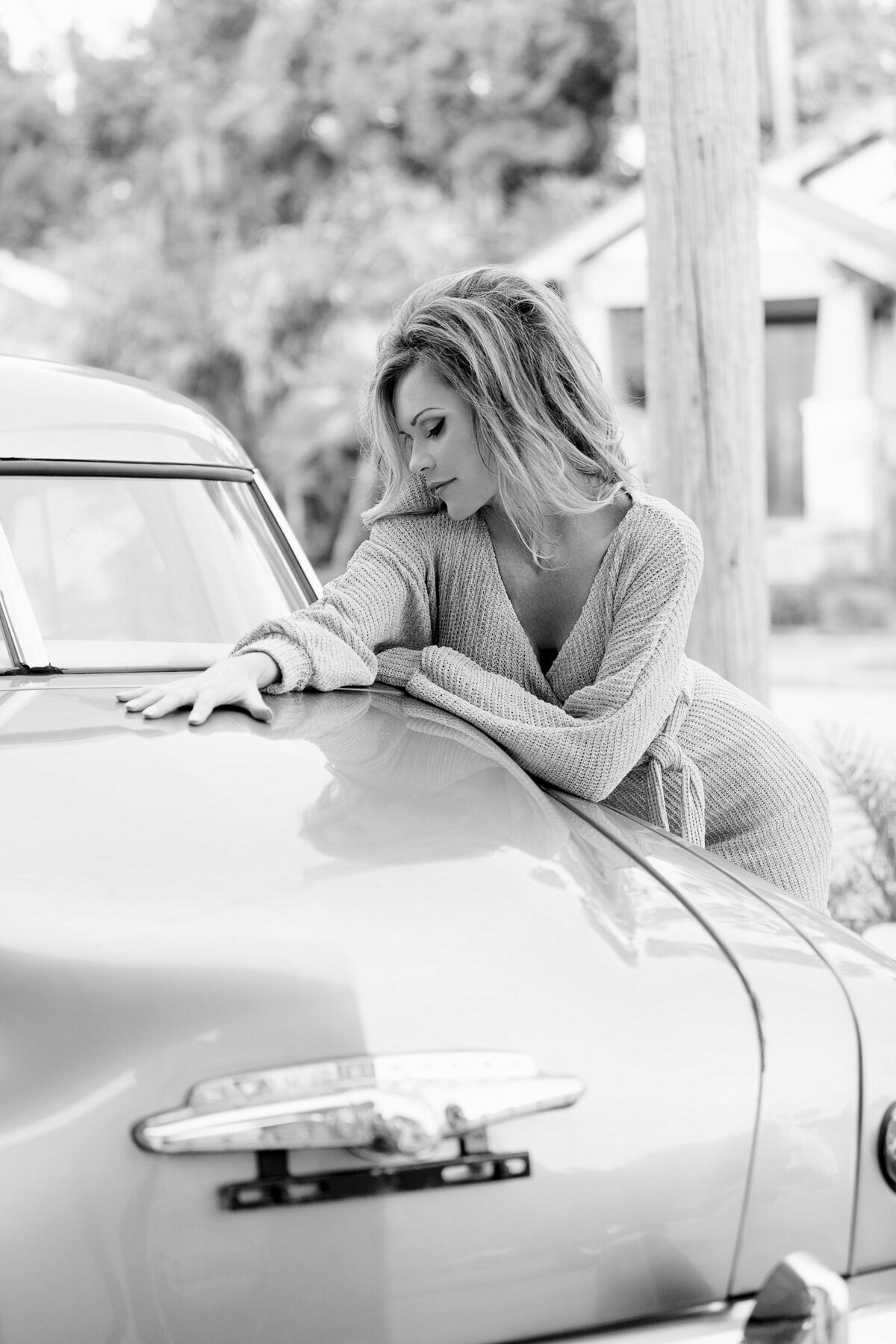 woman laying on classic car