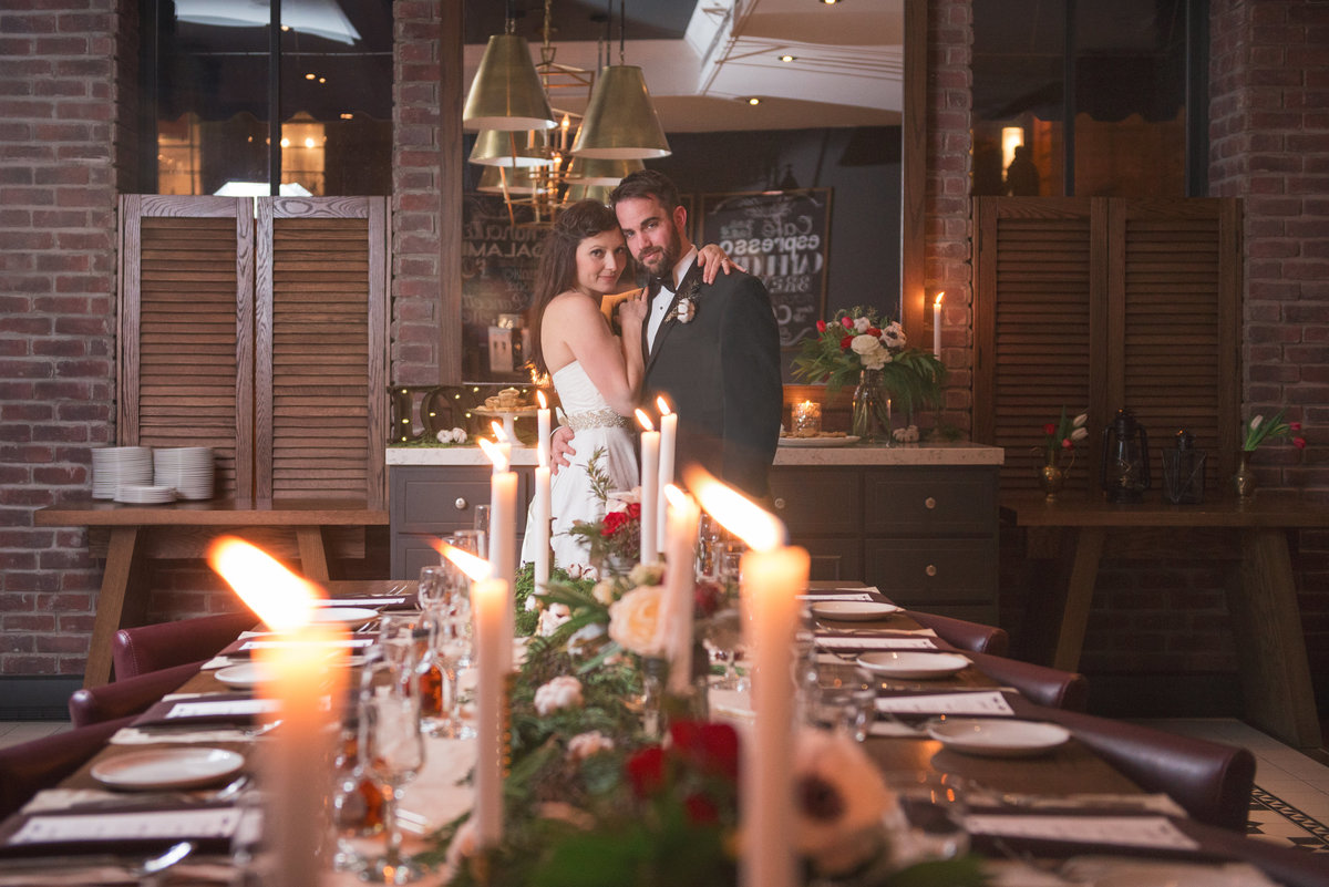 bride and groom standing at harvest table at the Albion rooms by candlelight