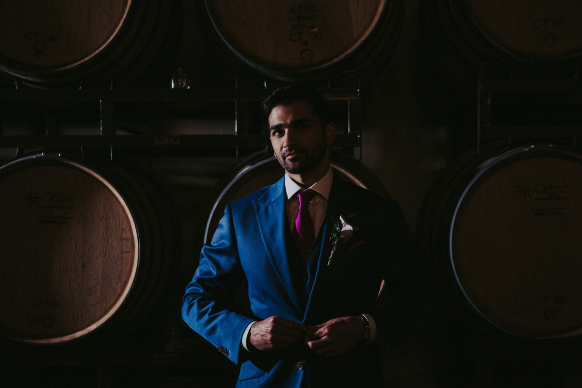 Callaway winery wedding pictures groom poses in front of wine barrels