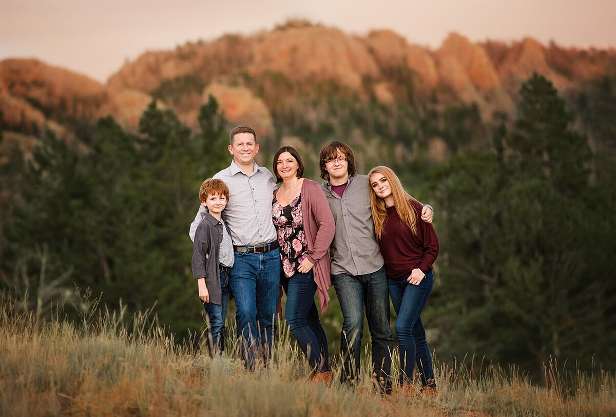 Three kids with their parents in front of evergreen trees by the mountain by Laramie.