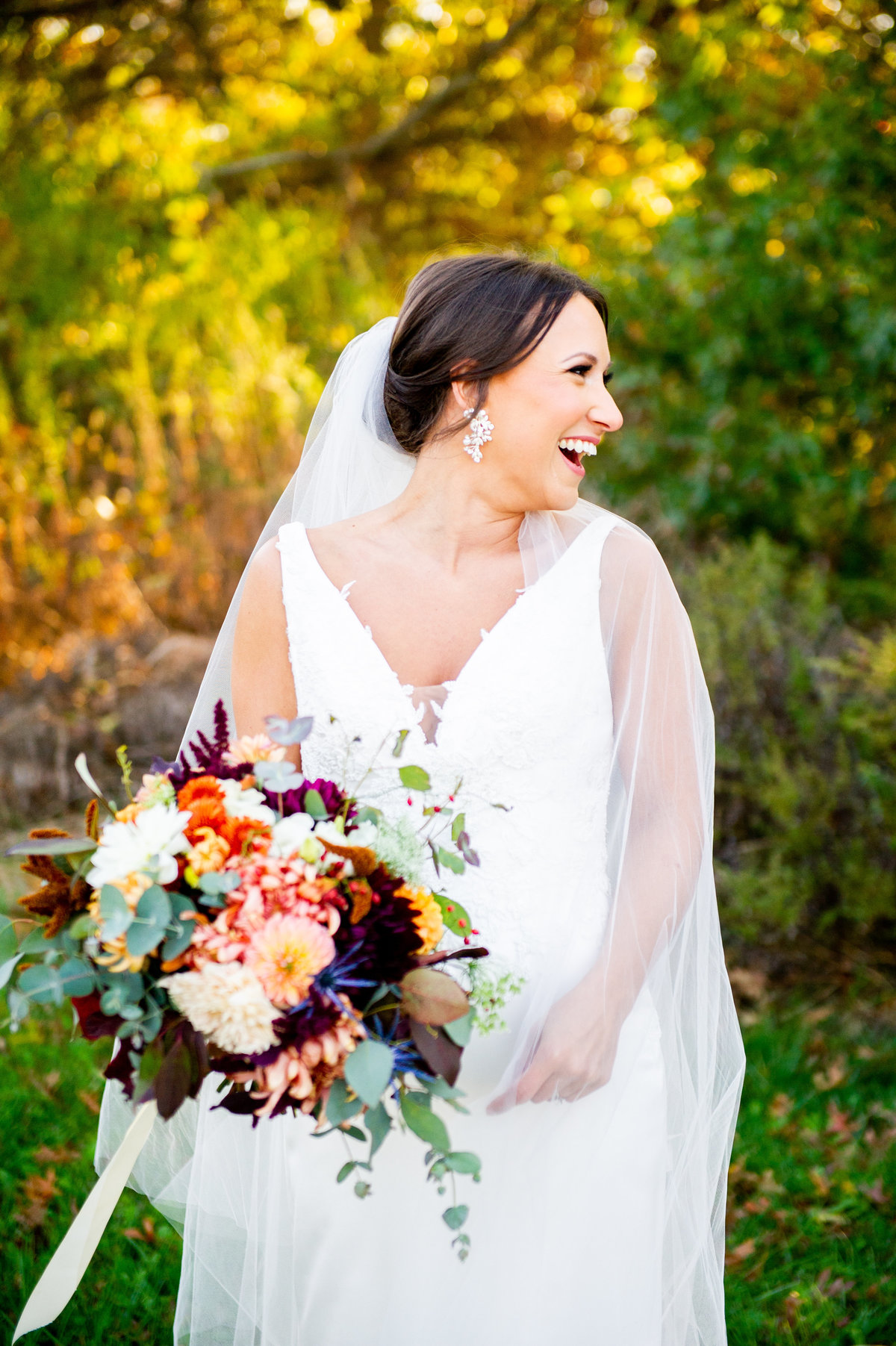 fall bride looks to side and laughs