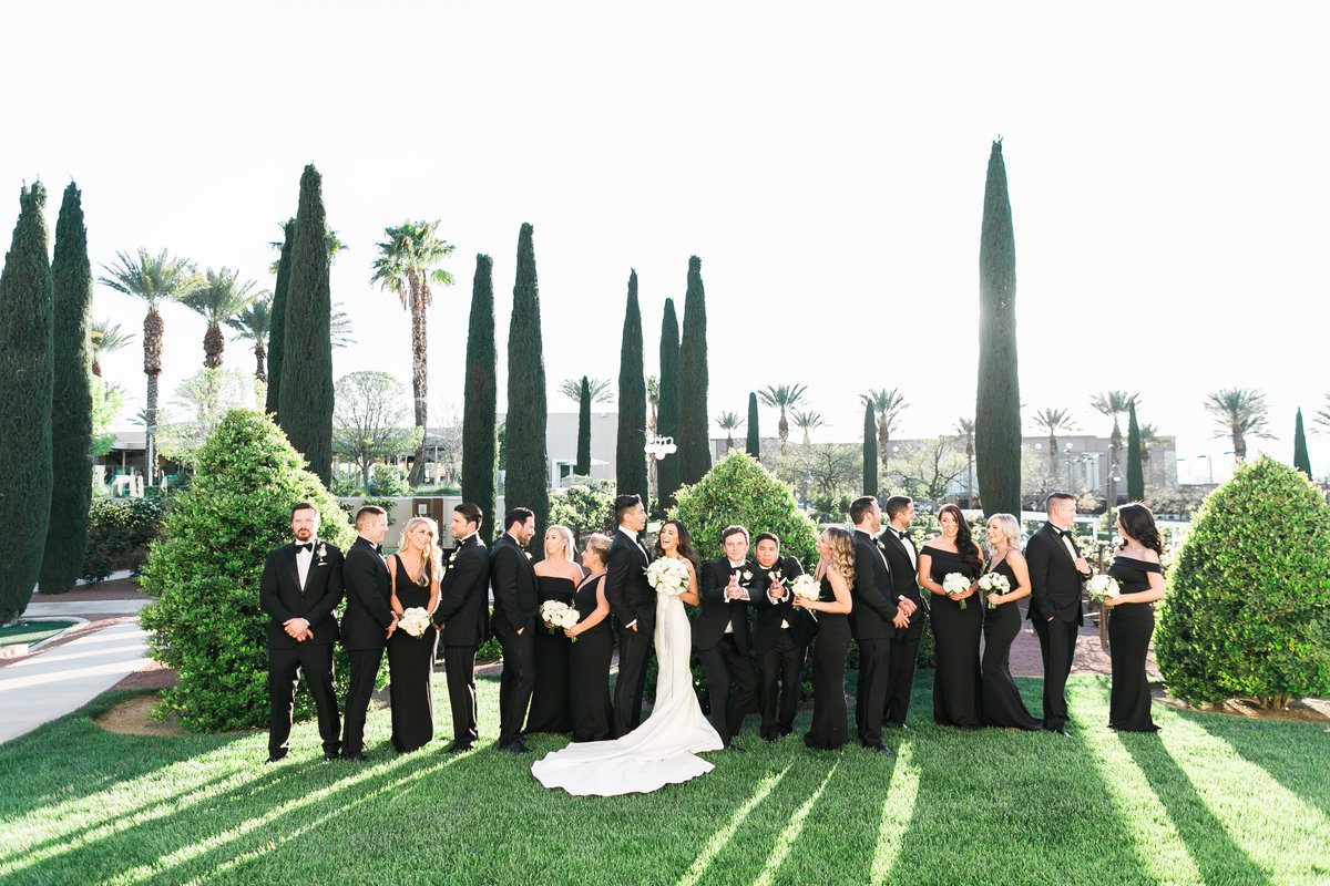 a photo of a bride and groom with their bridal party in black bridesmaids dresses and black suits at the Green Valley Ranch Resort and Spa in Las Vegas