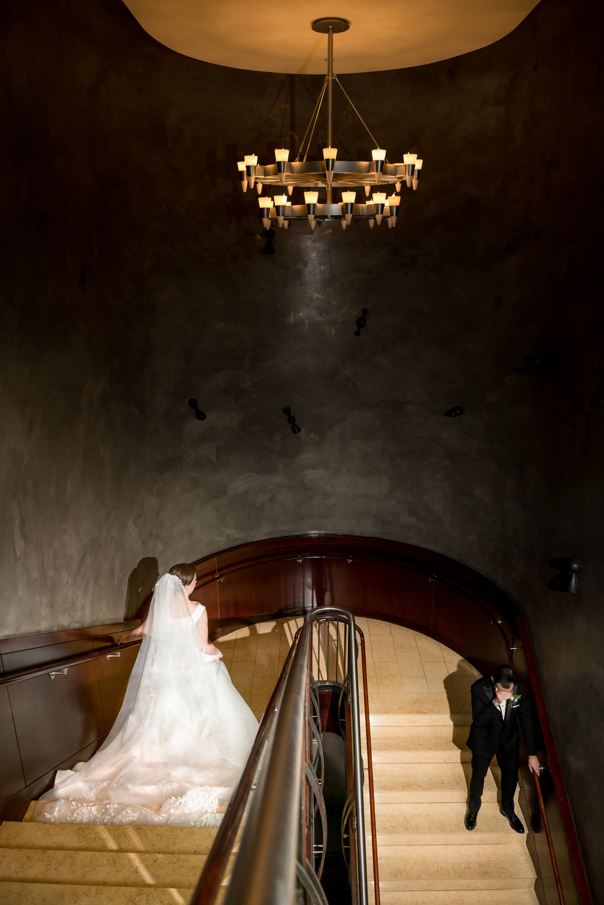 couple approaching their first look on a grand staircase