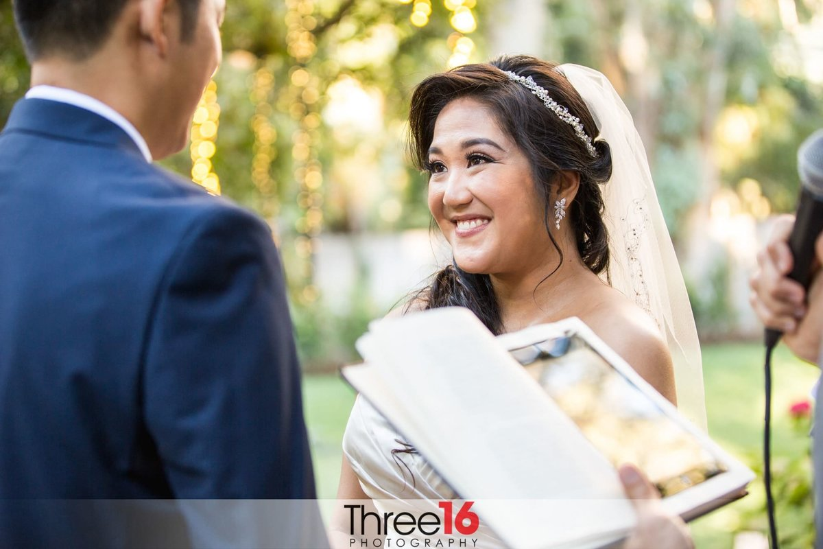 Stunning Bride smiles at her Groom during wedding ceremony