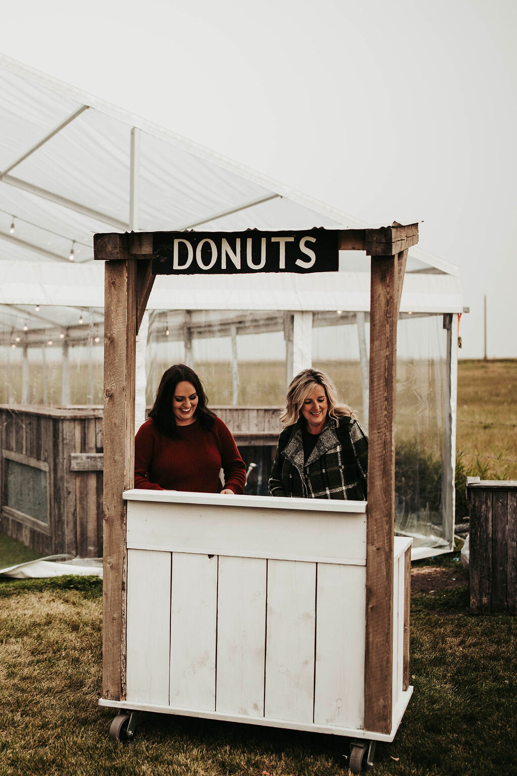 women standing at a donut stand