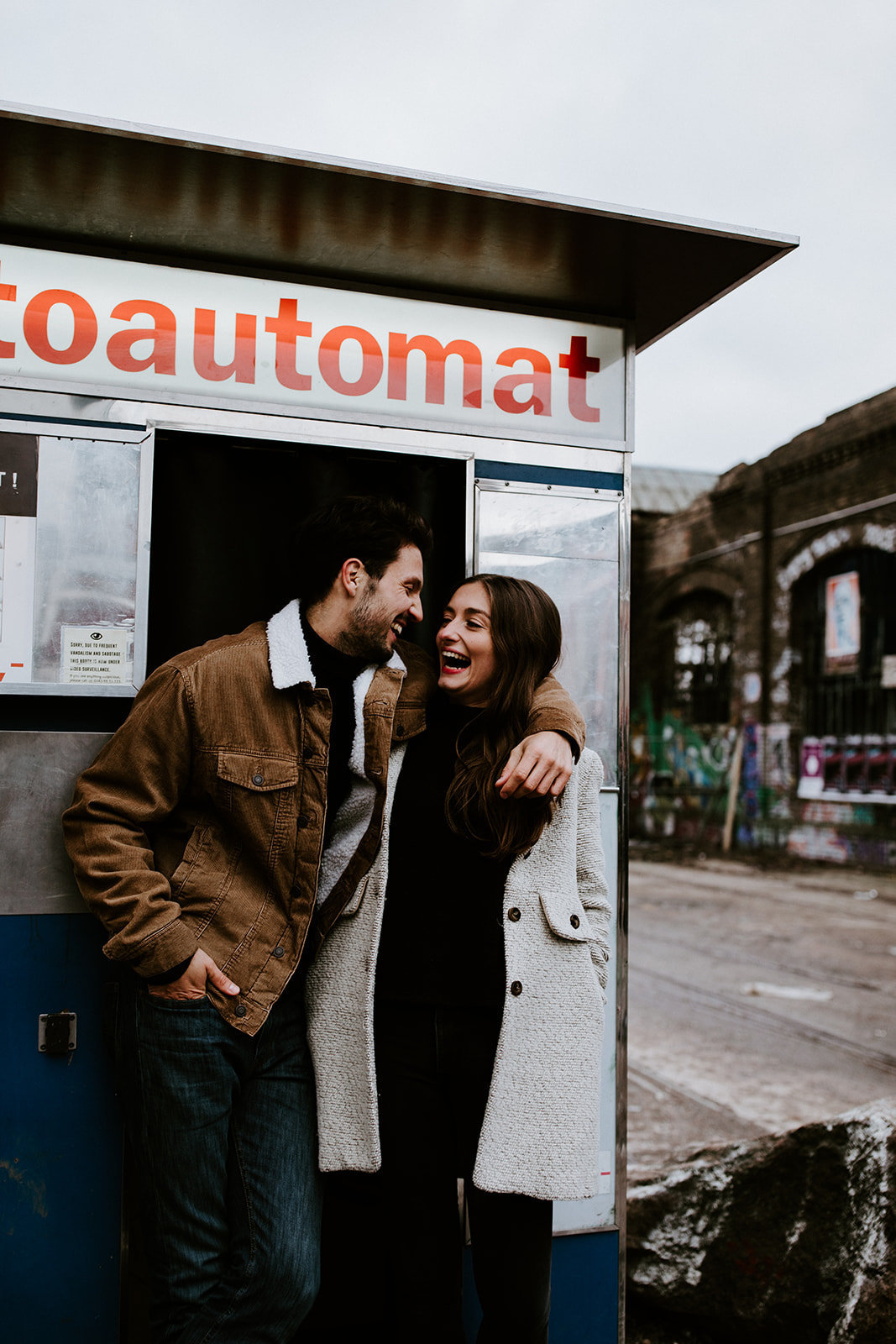A man and woman stand in front of a photo booth.