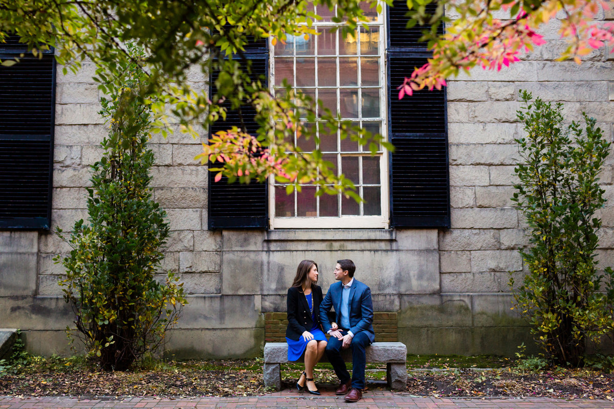 The couple sits in front of a stone church in Portland Maine
