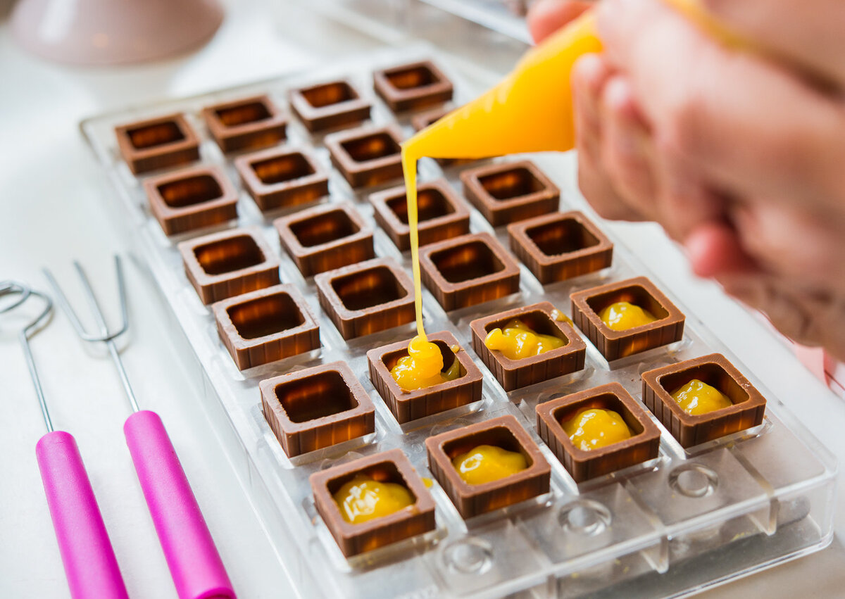 Handmade chocolates being filled with mango puree