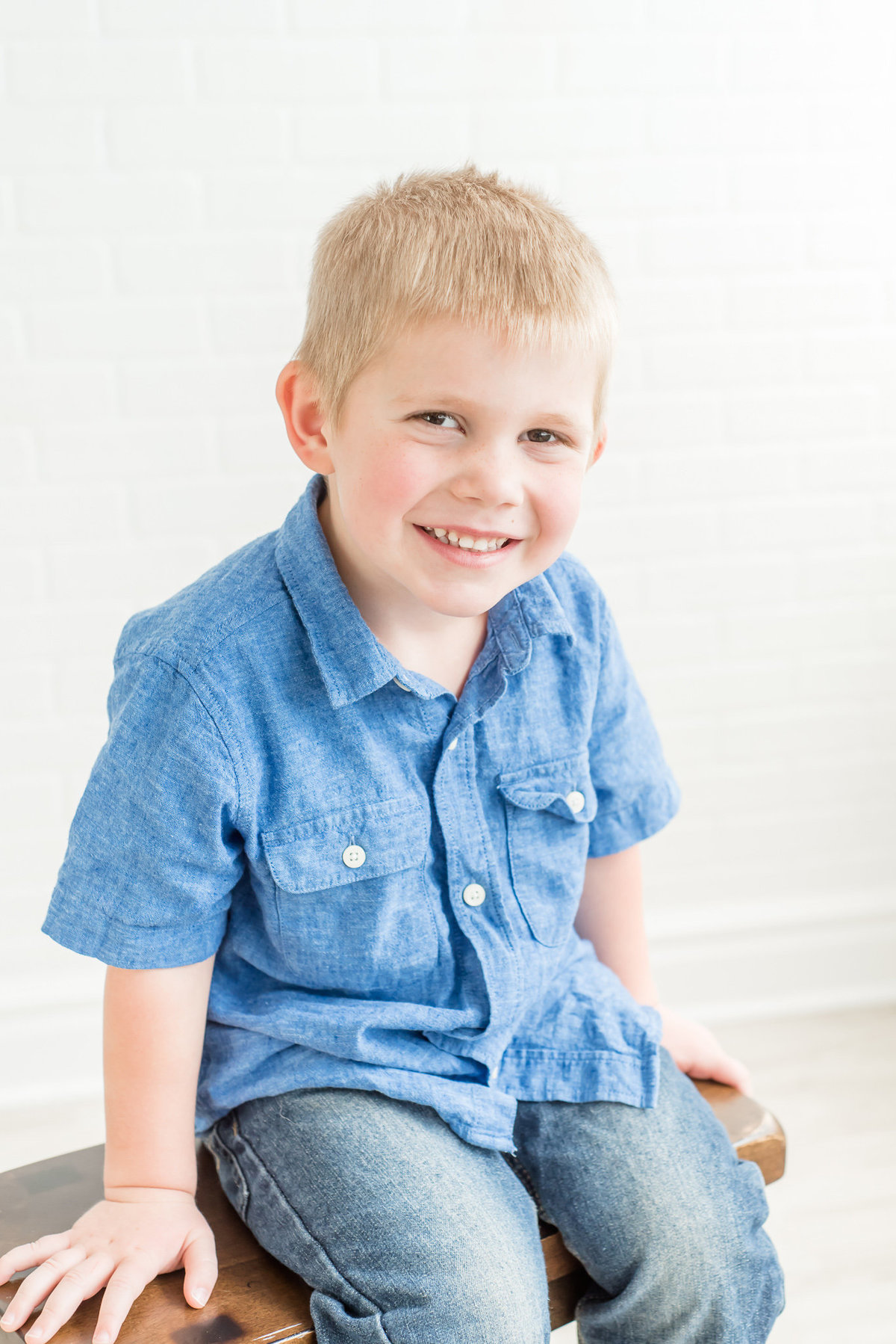 boy smiles at the camera while sitting on a stool