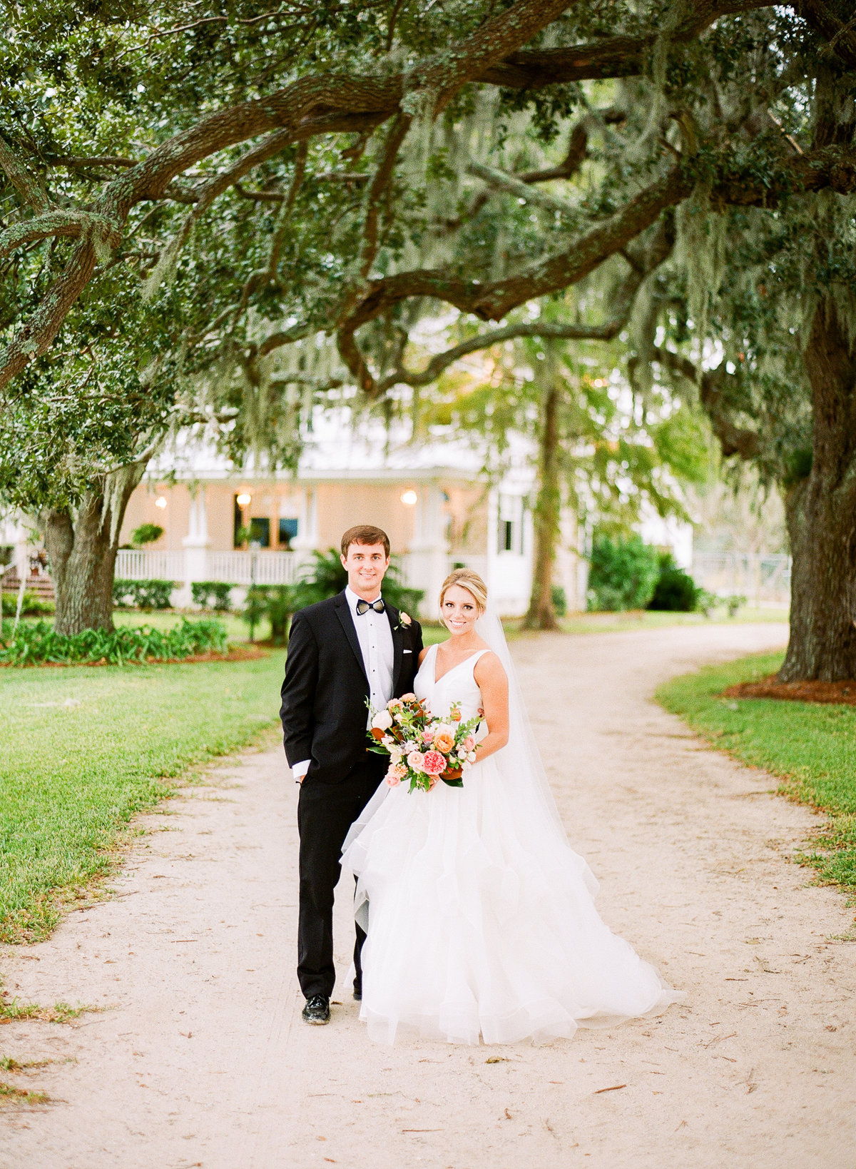 Classic Charleston Newlyweds Stand in front Classic White Plantation House under Spanish Moss Live Oaks Trees