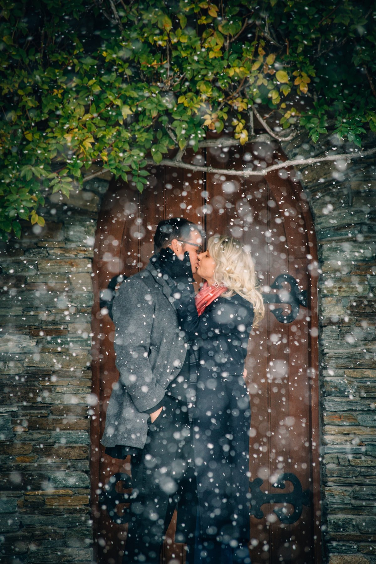Bride and groom kissing in the snow in front of an old chapel