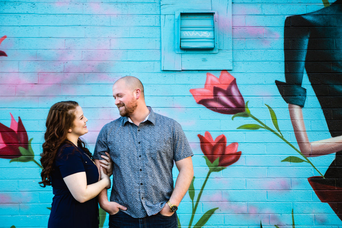 Couple looking at each other in front of blue floral art mural at Roosevelt Row by Phoenix engagement photographer PMA Photography.