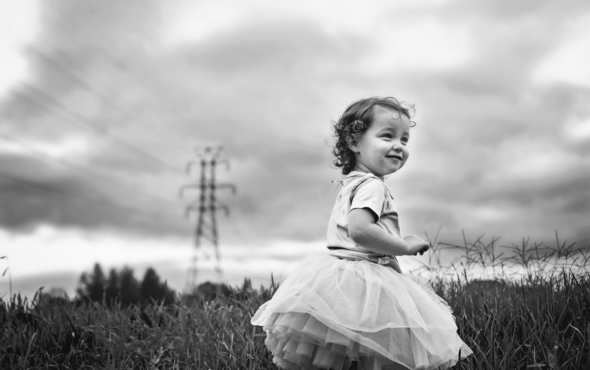 charlotte documentary photographer captures a day in the life with small child playing outdoors before a storm rolls in