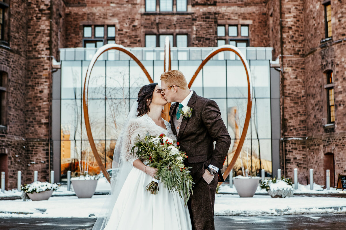Winter wedding with bride and groom kissing outside in front of Hotel Henry in Buffalo, New York