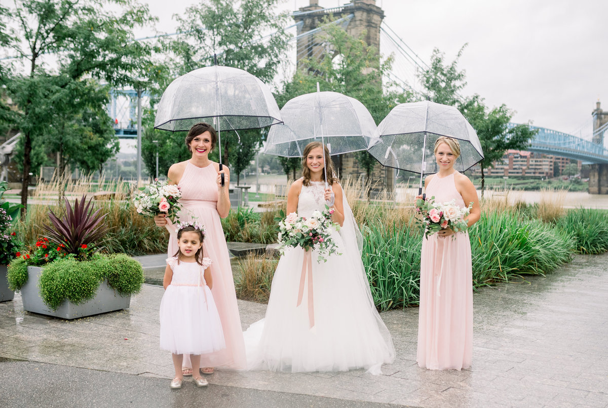 Bridesmaid in blush smile towards the camera as they stand with clear umbrellas during a rainy Cincinnati wedding