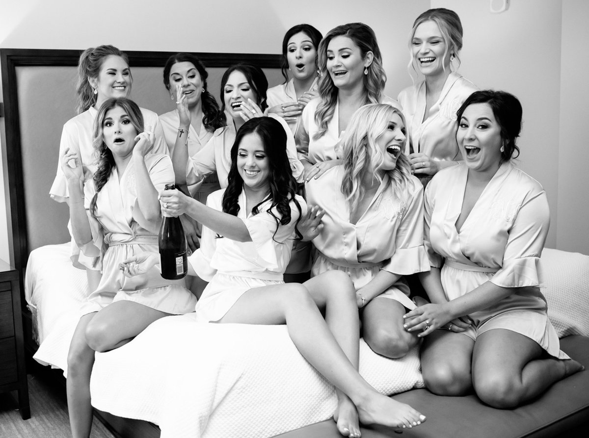 bride opens champagne on the bed with her bridesmaids at the NOPSI nola