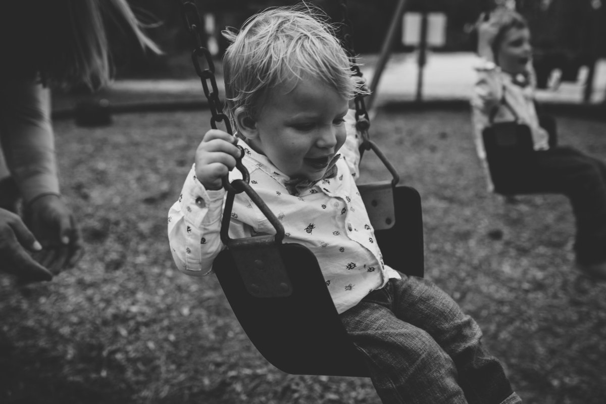 Toddler smiling on swing at omaha park during family session