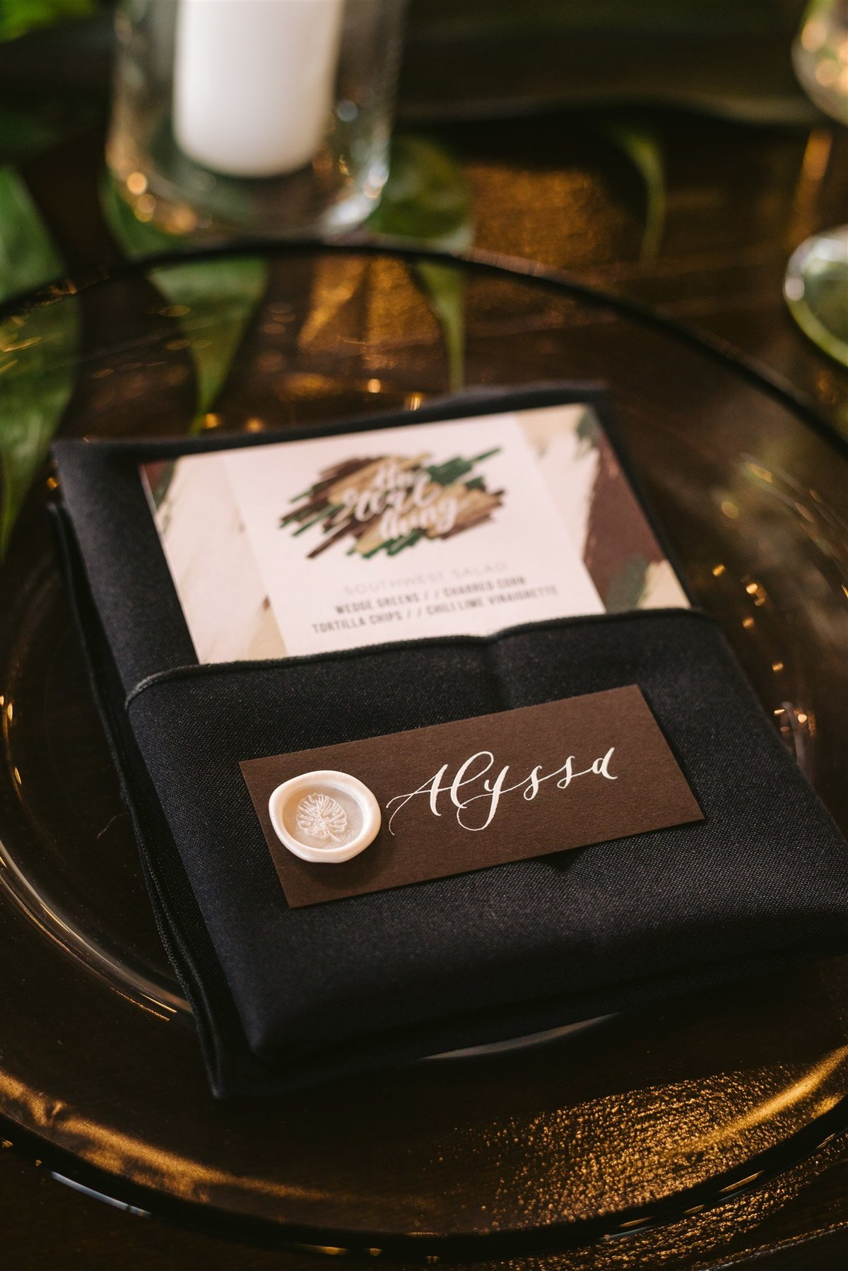 clear charger with black rim and black napkin with menu card for modern reception