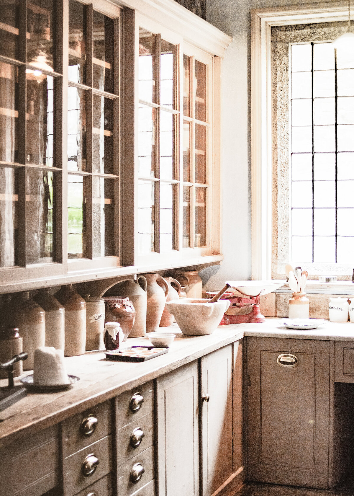 Natural wooden units hold traditional pottery milk churns in a rustic utility room.