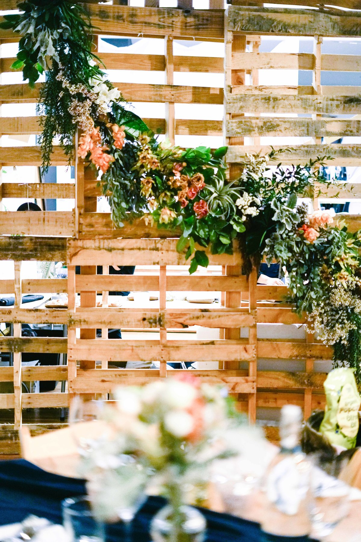 Dinner party backdrop using wood pallet and greenery garland with flowers