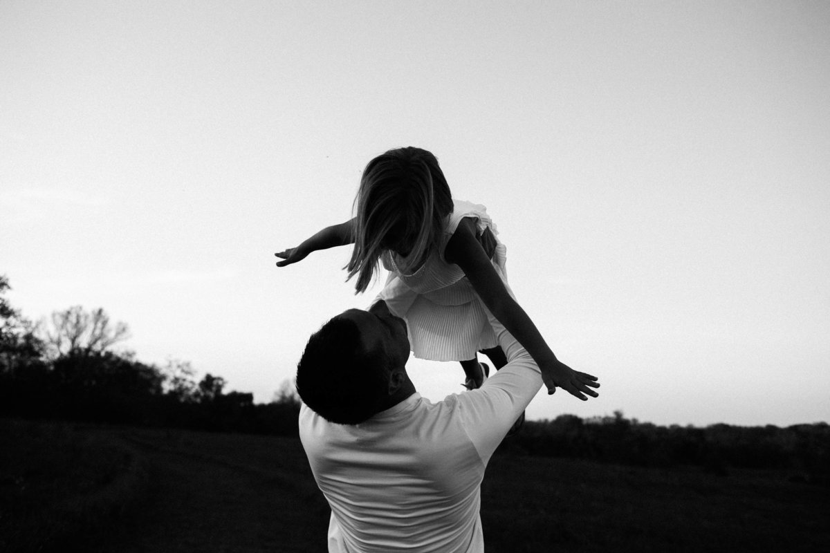 Dad holding daughter in air playing airplane during sunset session, Elle Baker Photography