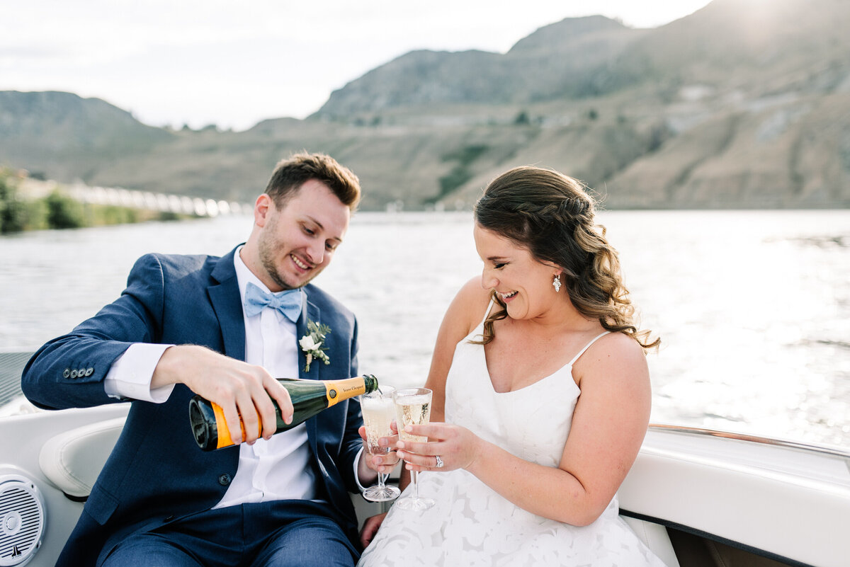 Bride and groom preparing a champagne toast on a boat during a Lake Chelan wedding