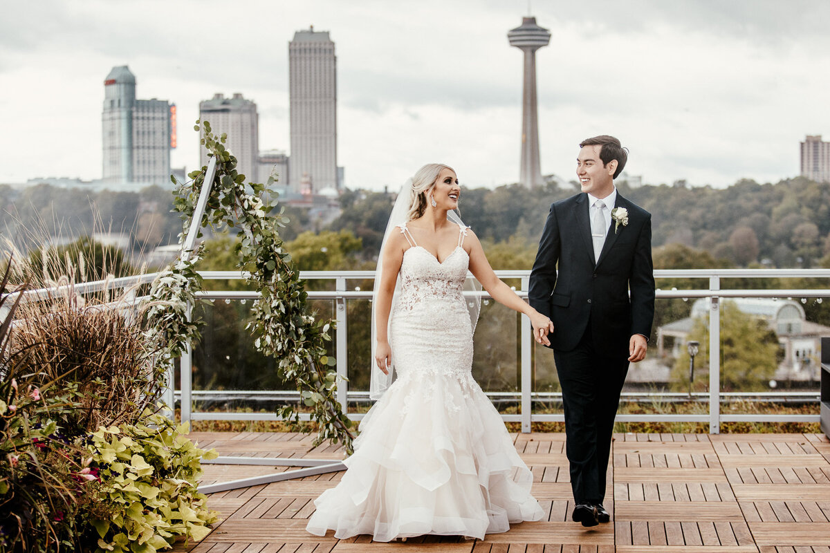 Bride and Groom holding hands with city backdrop in Niagara Falls State Park, NY