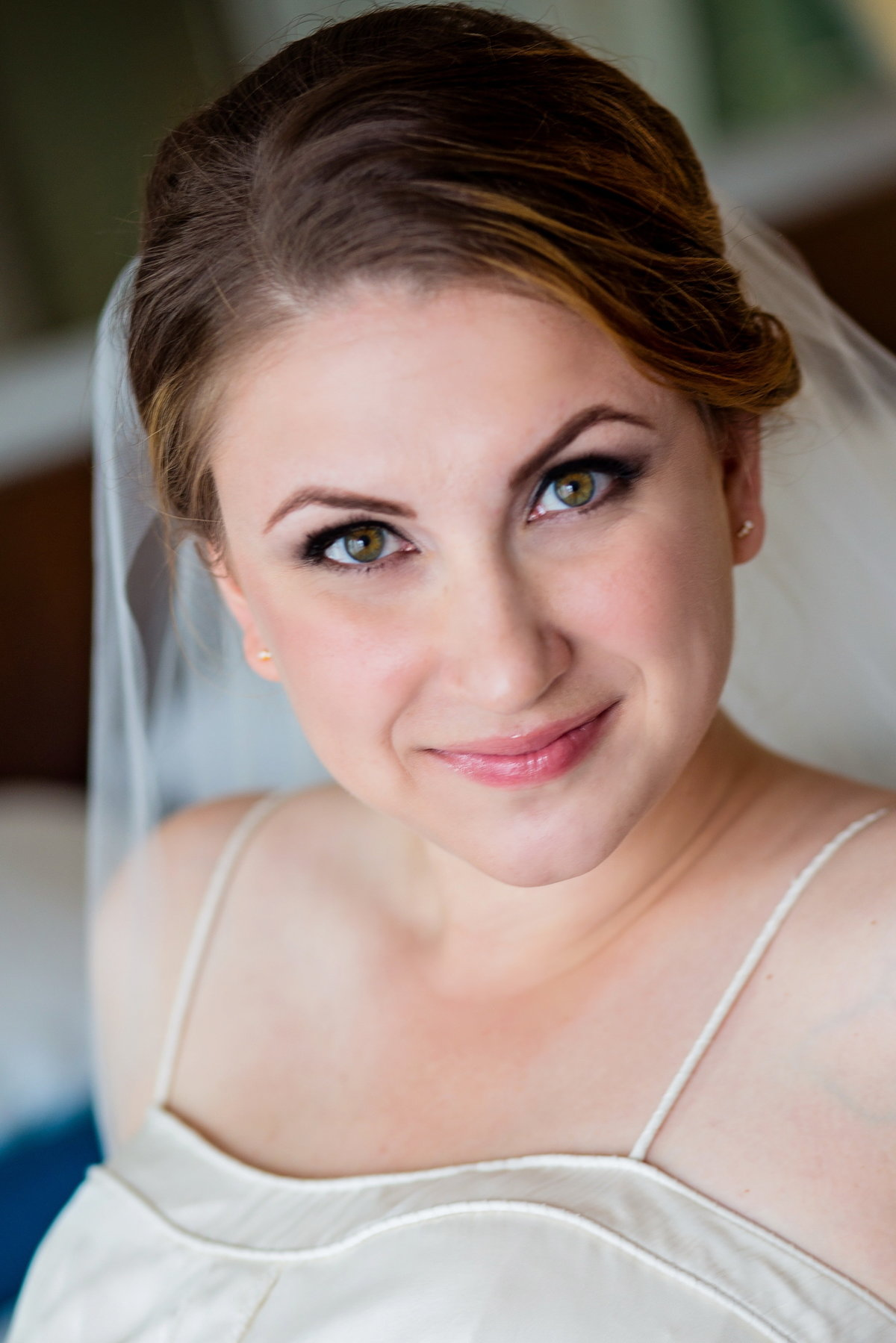 Close up portrait of bride, detailing makeup and top of dress