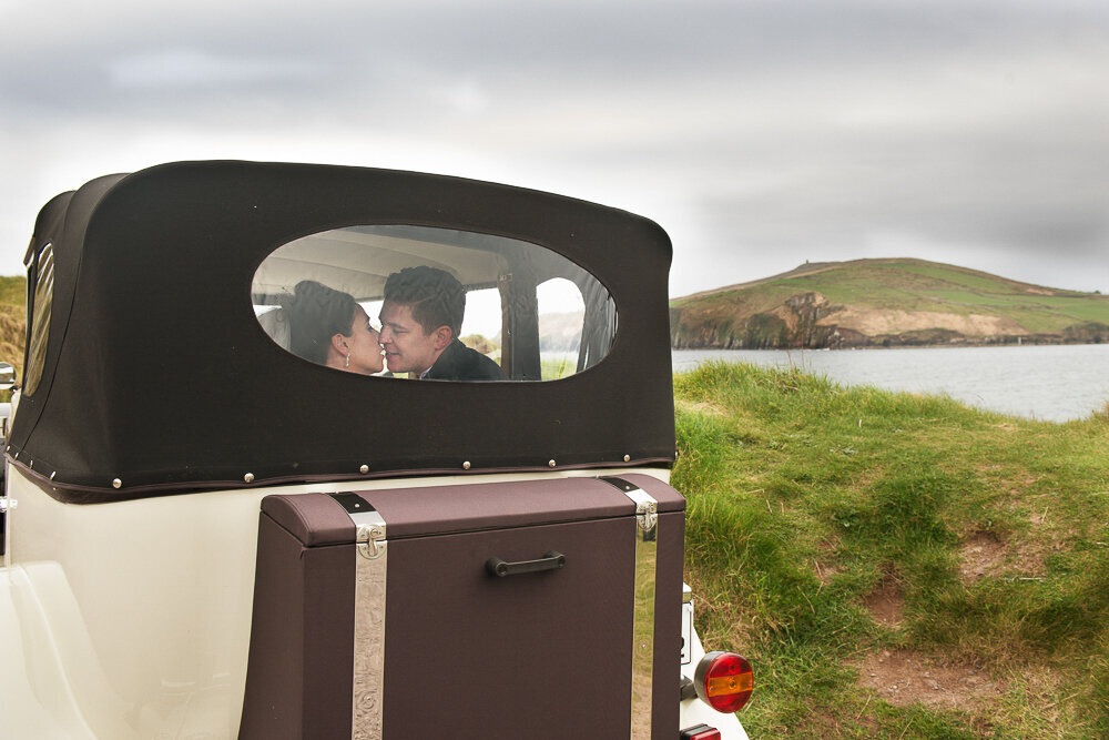 bride and groom kissing in a vintage, soft top  car while parked at Bin Ban beach in Kerry