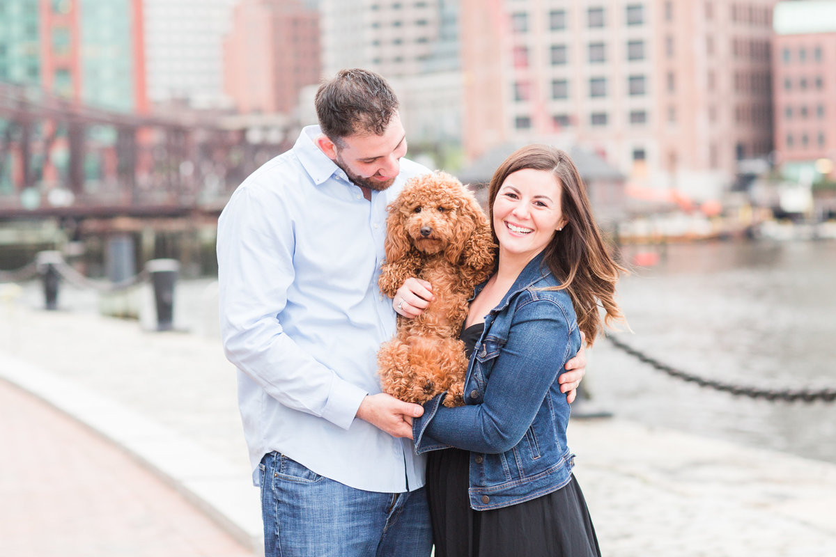 Man and wife holding their mini goldendoodle with Boston skyline in the background