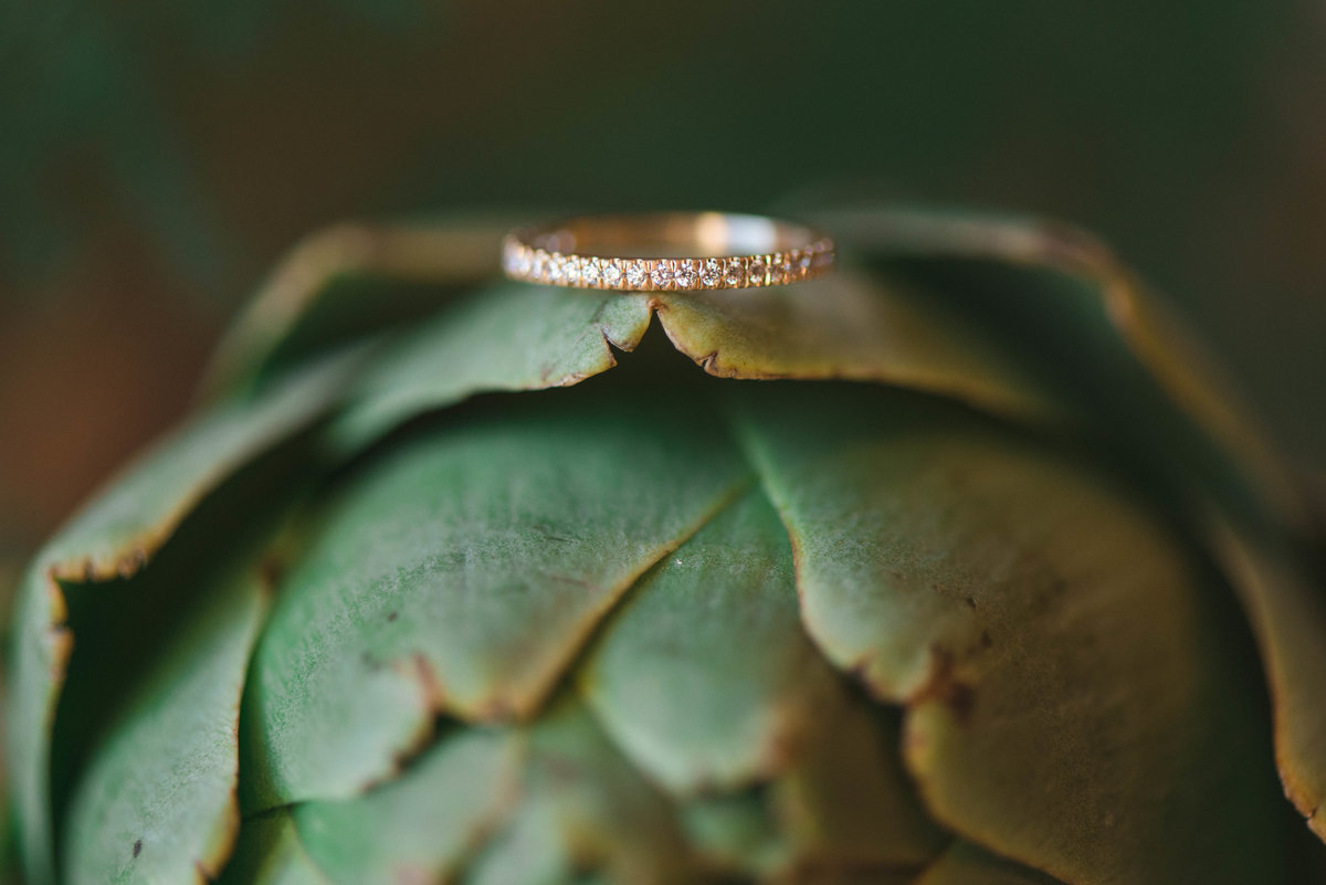gold wedding band with diamonds sitting on top of an artichoke