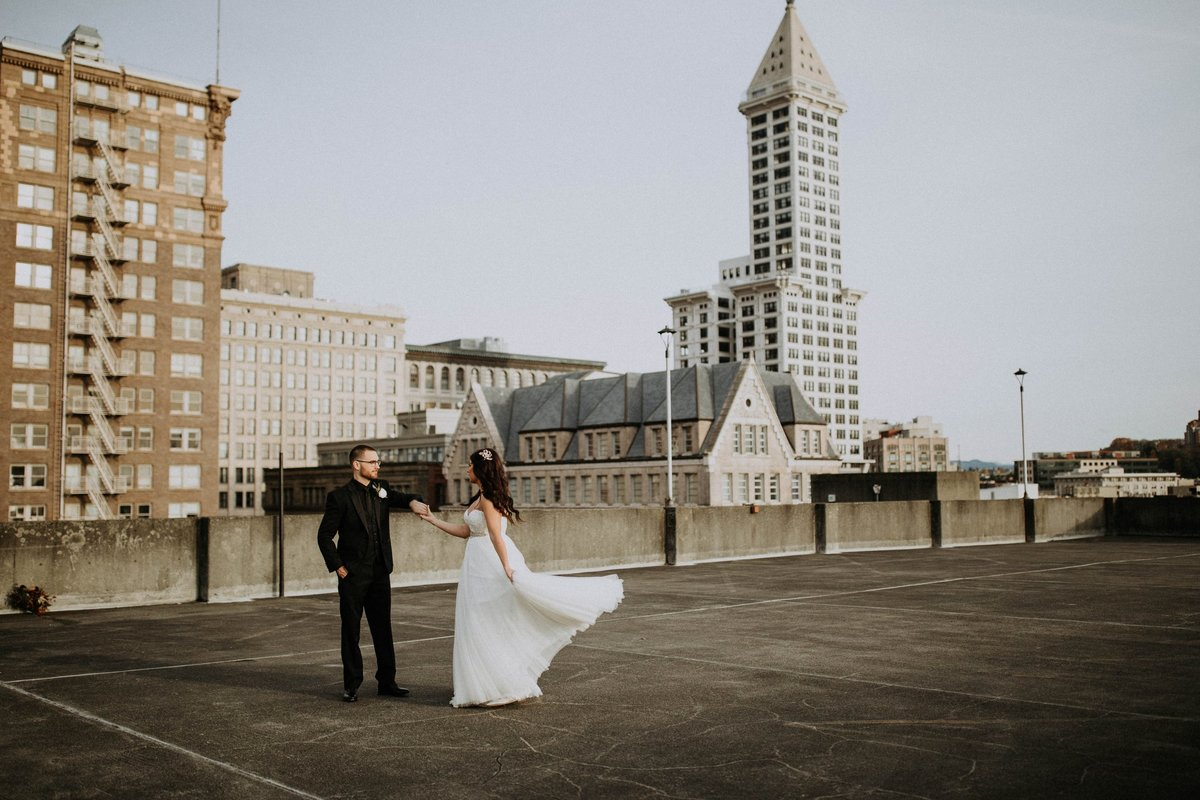 Bride and Groom dancing on rooftop overlooking The Rainier Club and Smith Tower