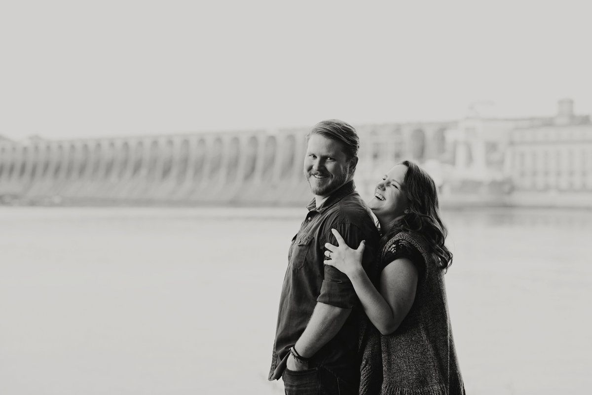 Couple cuddling and laughing  at wheeler dam engagement session