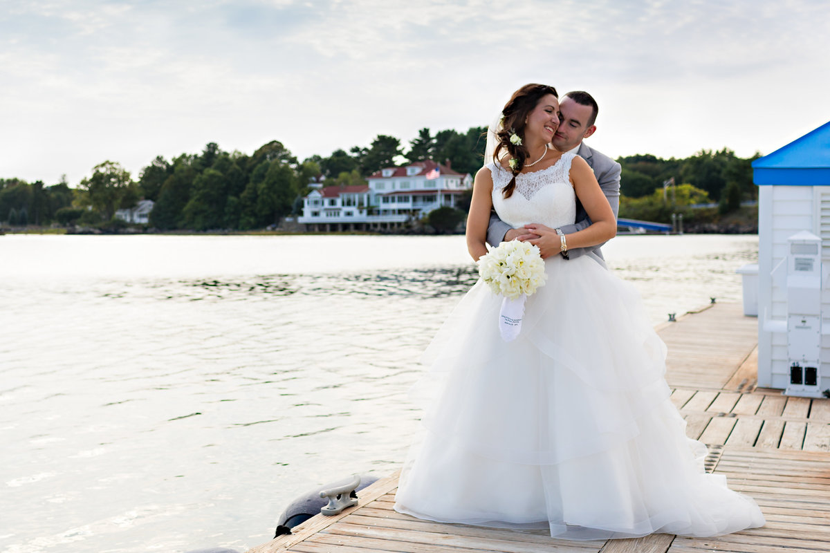 Rye New Hampshire Wedding Photographer with the couple embracing on the docks out by the boats and the ocean in the summer