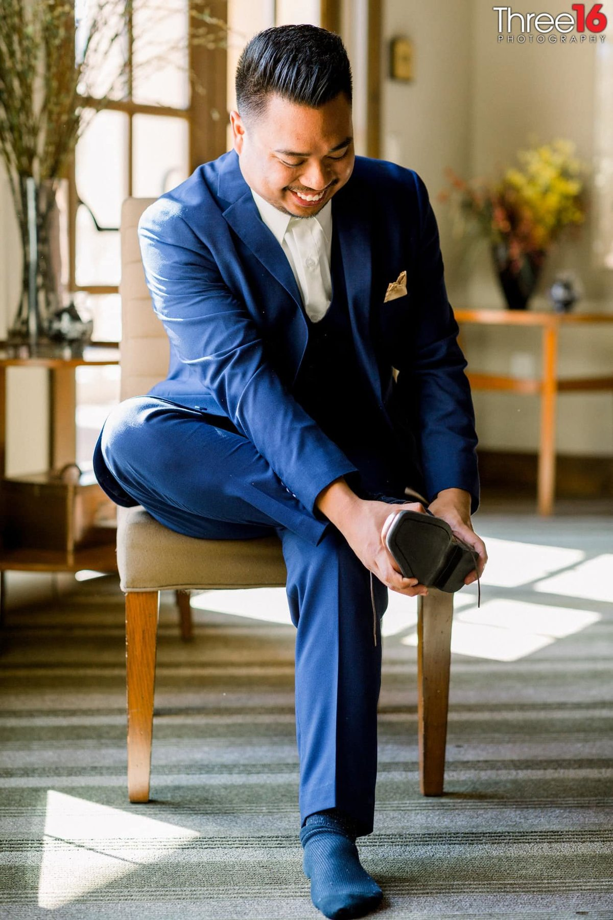 Groom putting on his shoes before the ceremony starts
