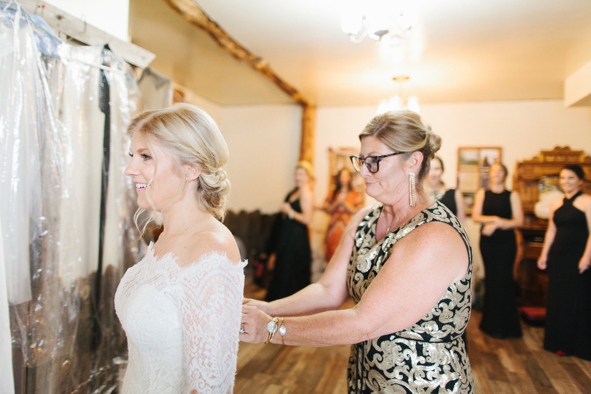 A mother helps button up her daughter's wedding dress.