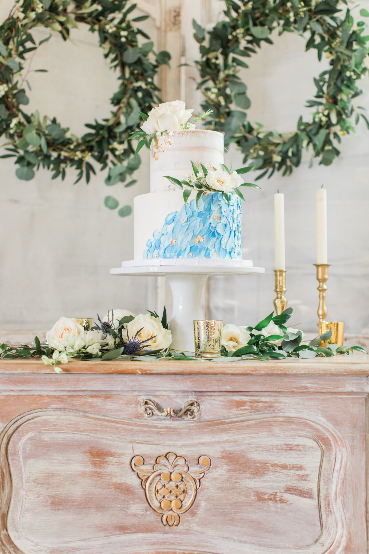A blue and white wedding cake on a gorgeous vintage table, there are candlesticks in the background and the table is decorated with florals. There are two green wreaths in the background