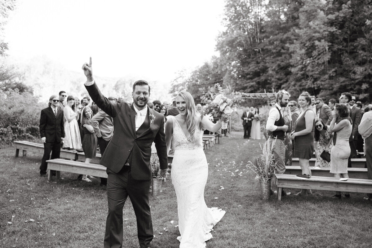 A bride and groom raise their arms in celebration after just having finished walking down the aisle at an outdoor wedding