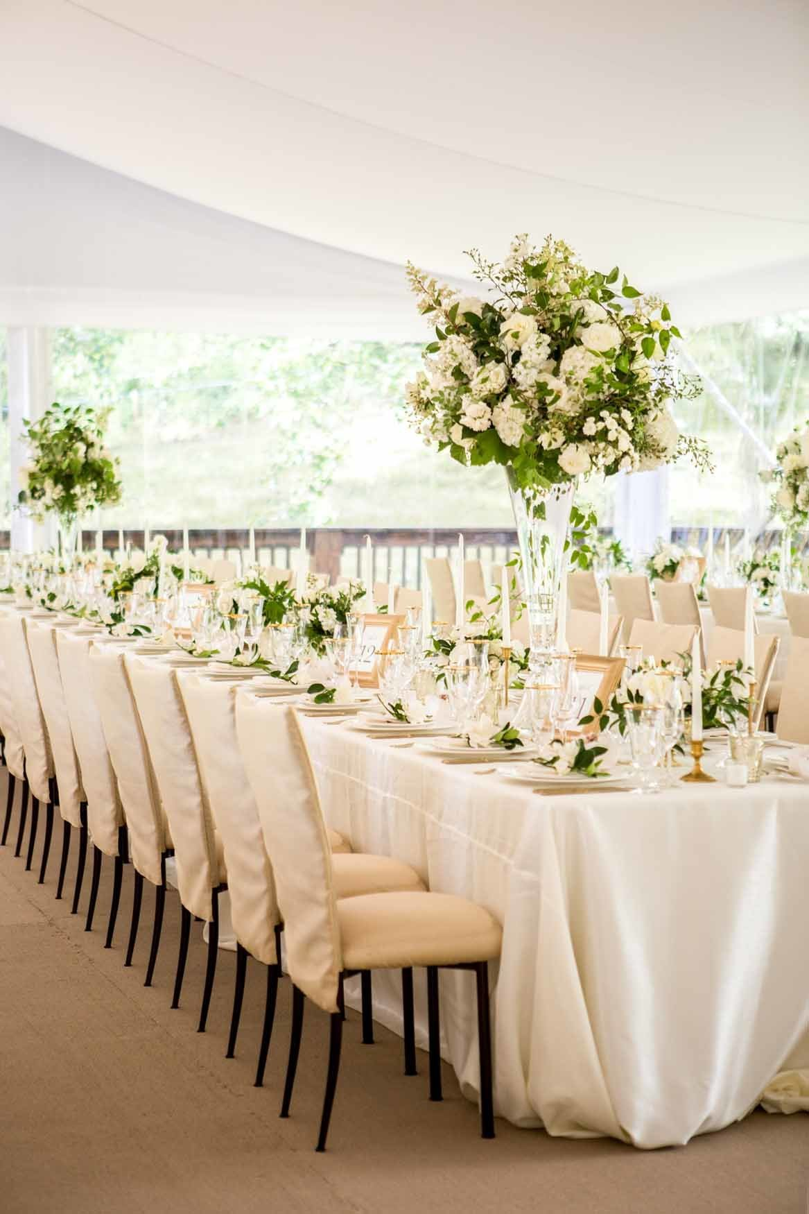 White summer tent wedding reception with white and green floral