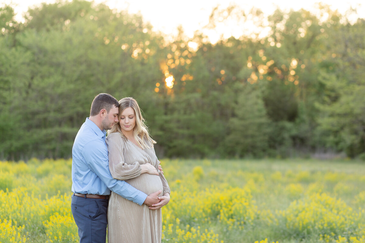 Spring Sunset Maternity Session with gold maxi dress standing in yellow flower field  at Busch Wildlife in St. Louis by Amy Britton Photography Photographer  in St. Louis
