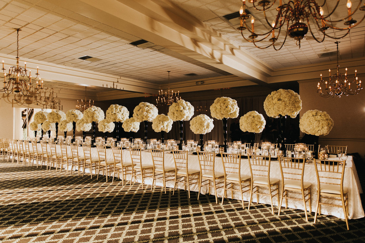 A luxurious tablescape set for 50 guest with floral arrangements to the ceiling and gold chiavari chairs