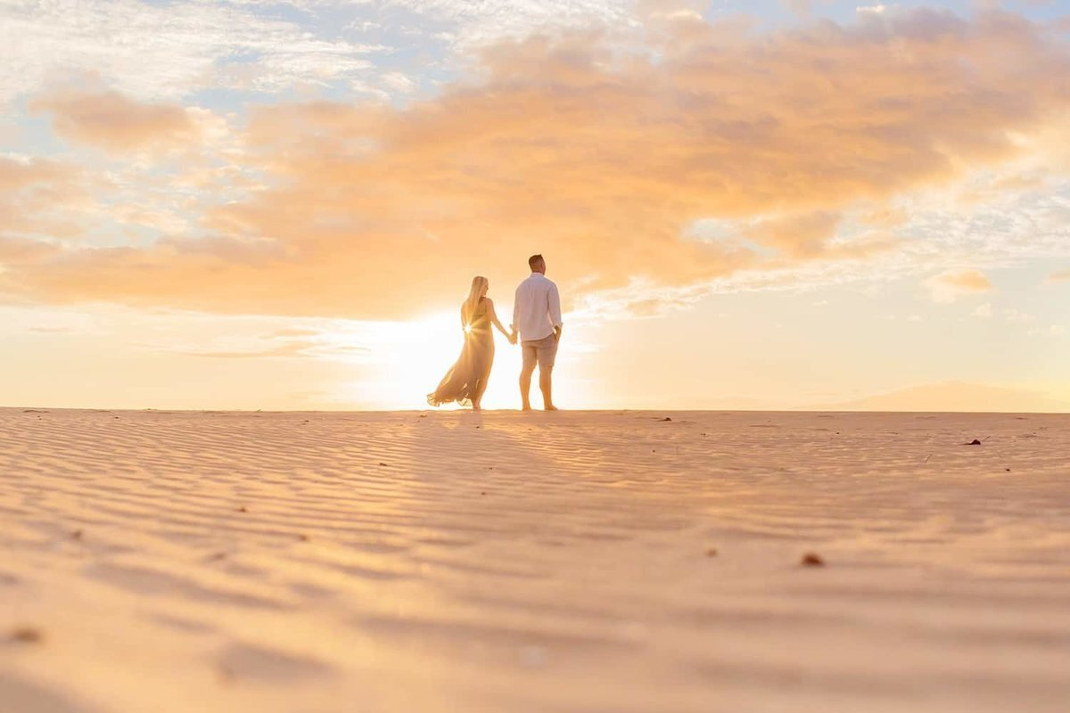 Wide shot of couple holding hands at sunset with textured sand in foreground