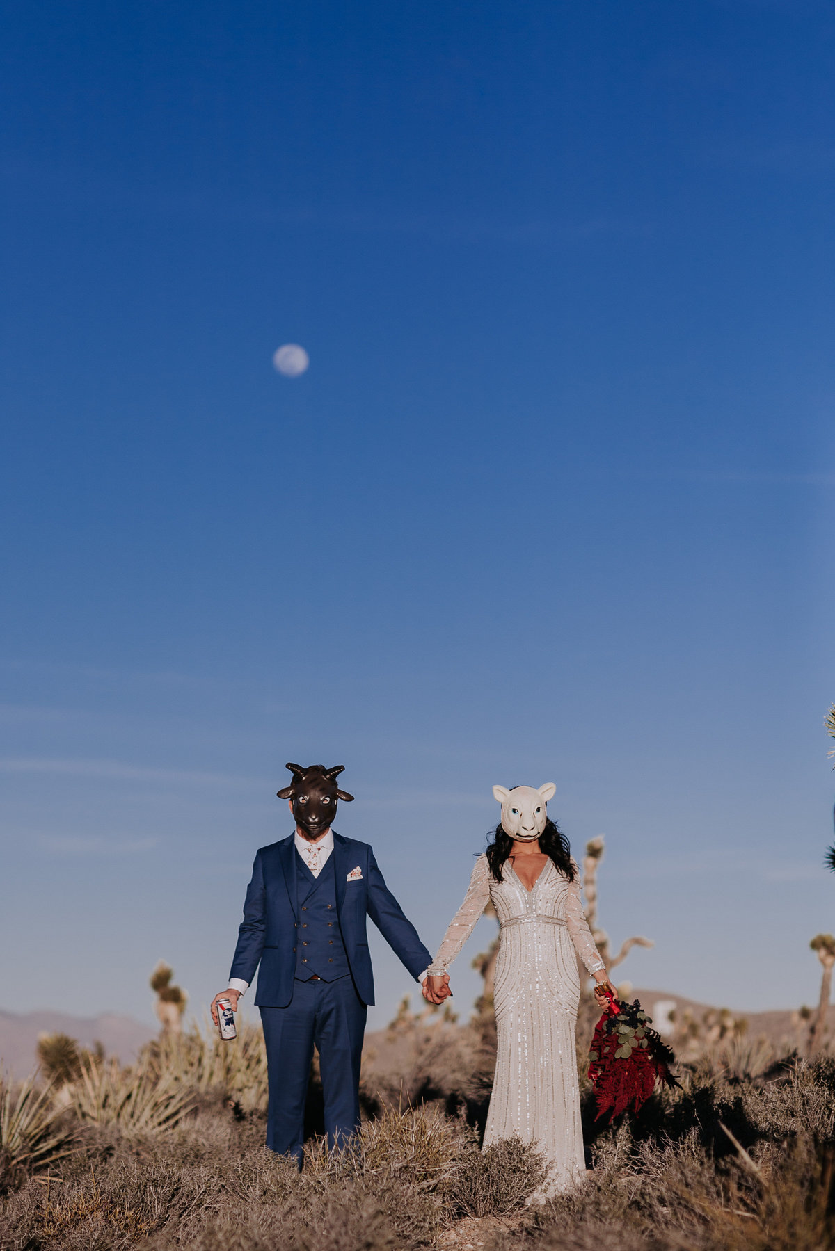 Lake Tahoe elopement photographers bride and groom pose under full moon in desert wearing animal masks