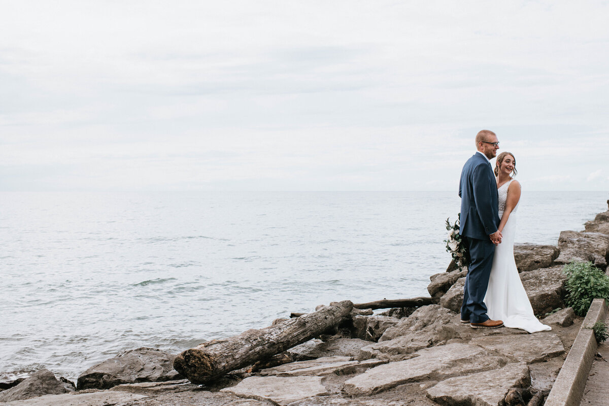 bride and groom holding each other on rocks by the ocean