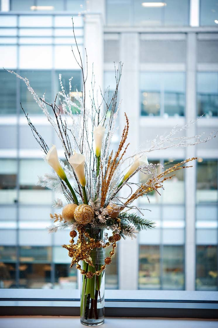 tall holiday centerpiece with white calla lilies, sparkle branches, gold ornaments, and sparkle garlands for Seattle holiday party