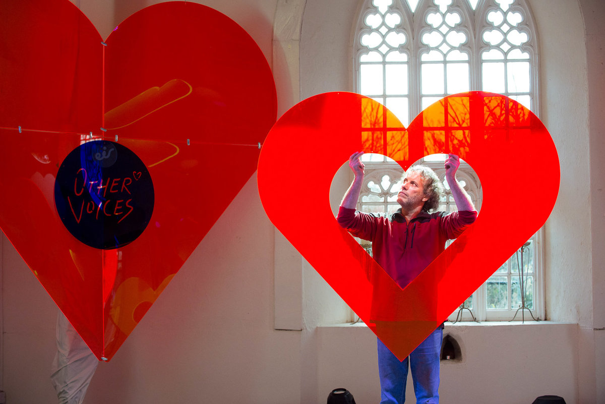 Set designer holding props for Other voices stage in St. James church, Dingle