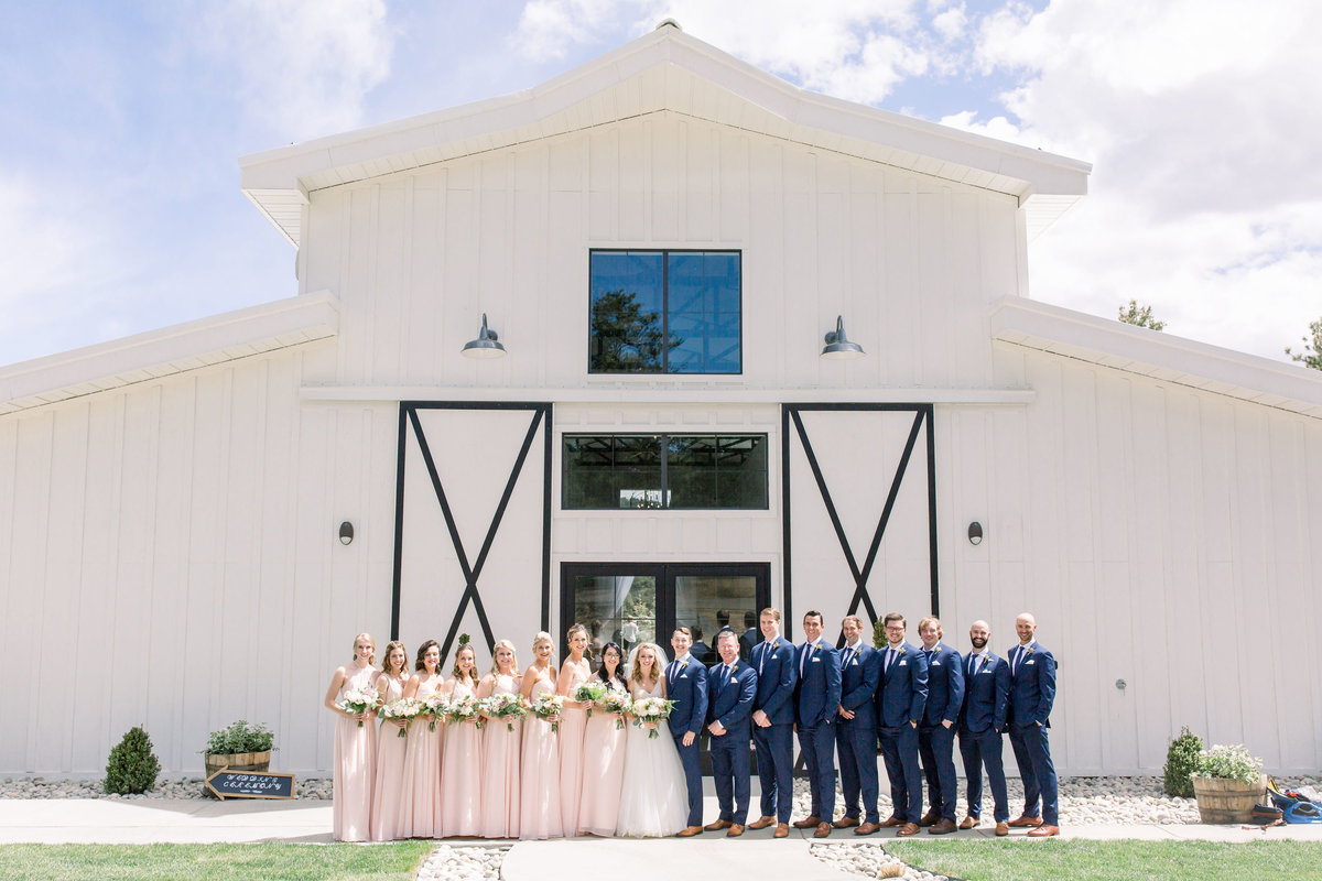 Bridal party standing in front of white barn at Woodlands Colorado wedding