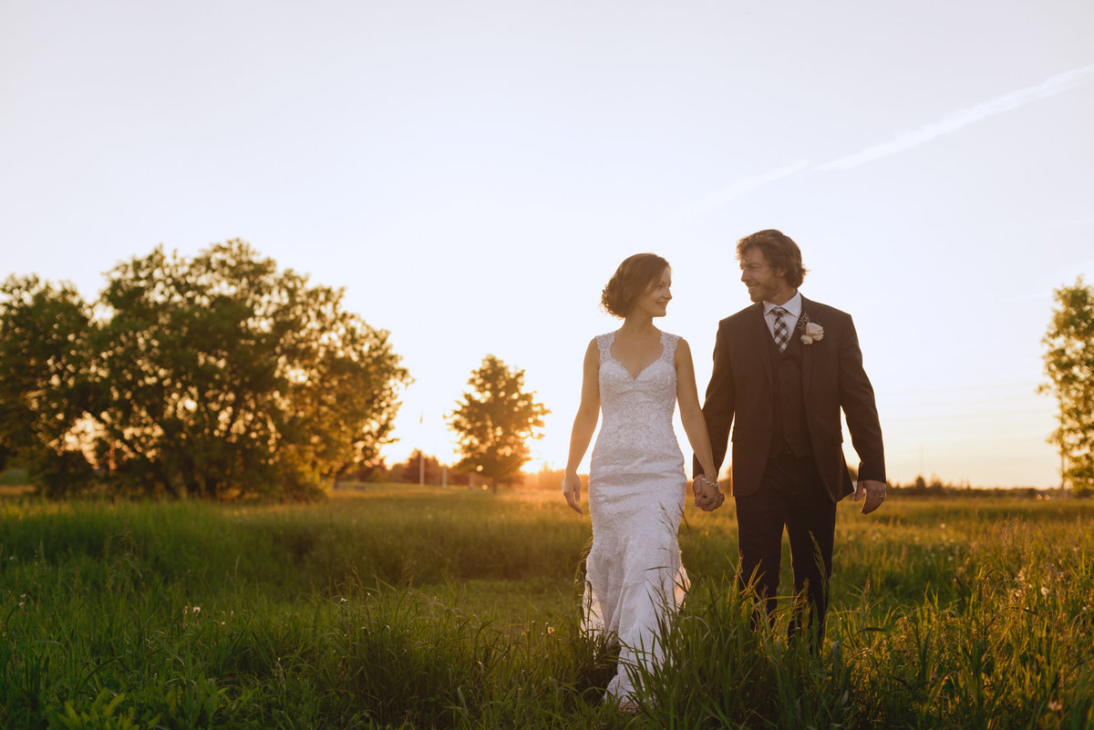 bride and groom walking through a field at sunset