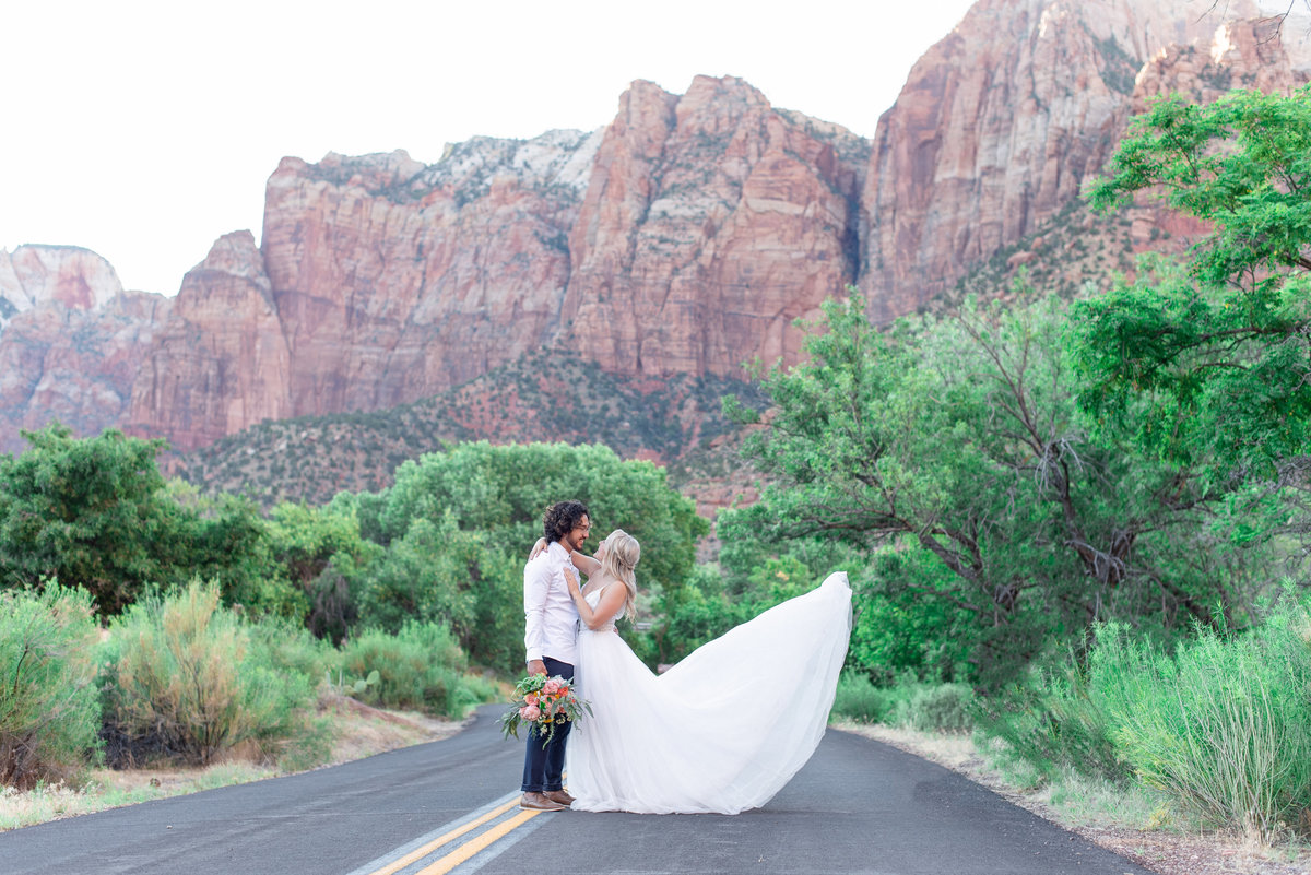 bride and groom hug at zion national park as her dress flies behind her