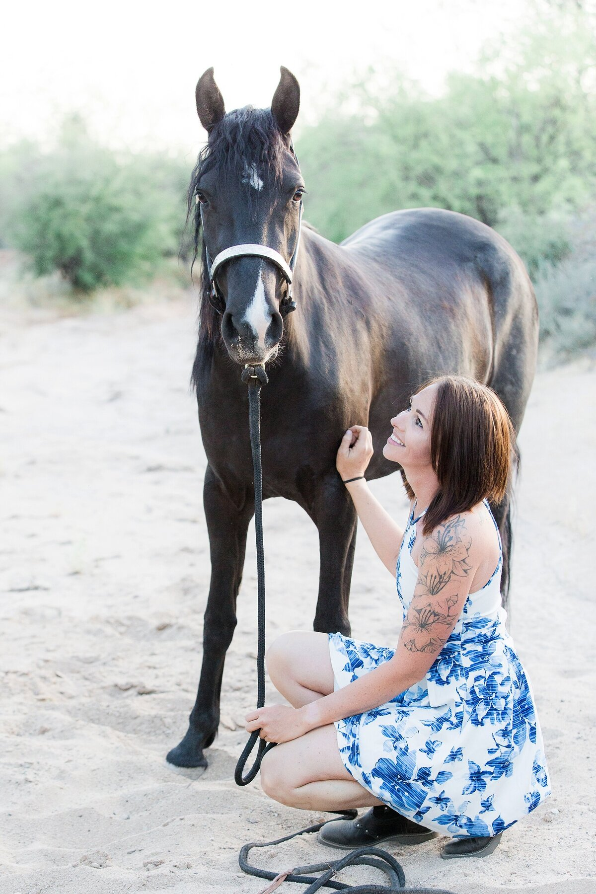 girl kneeling in front of her horse, looking up at her while her horse looks at the camera